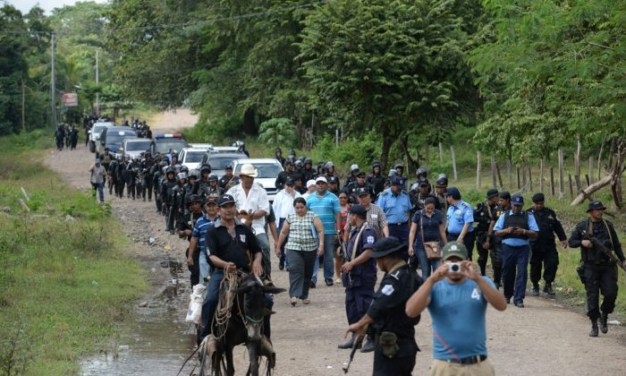 Riot police enter the town of El Tule, Nicaragua after they cleared a roadblock erected by residents, Wednesday, Dec. 24, 2014. National police special forces and soldiers fired tear gas and rubber bullets at demonstrators who had blocked the Pan American highway to protest against a proposed transoceanic canal. Thousands had maintained the roadblock since workers broke ground Monday for the $50 billion canal, which will require the expropriation of land. (AP Photo/Oscar Navarrete)