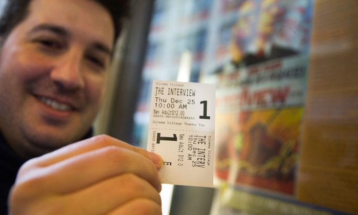 "Derek Karpel holds his ticket to a screening of ""The Interview"" at Cinema Village movie theater in Manhattan, N.Y., on Thursday, Dec. 25, 2014. Sony canceled the film's Christmas Day release after threats of violence by hackers linked to North Korea, but the release was reinstated in some independent theaters. (AP Photo/John Minchillo)"