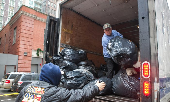 Volunteers from New York Cares unload over 3,000 bags of coats in New York on Dec. 23, that were donated by car dealerships and will be given to those in need. (Benjamin Chasteen/Epoch Times