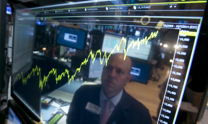 Specialist Jay Woods is reflected in a screen at his post that shows five years of the Dow Jones industrial average, on the floor of the New York Stock Exchange, on July 3, 2014. (AP Photo/Richard Drew)