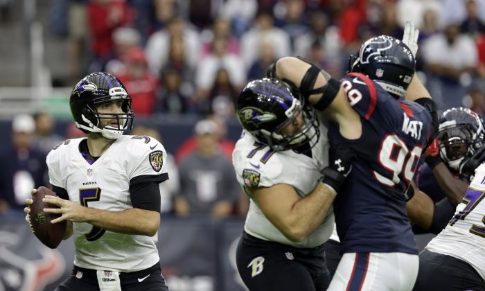Baltimore Ravens quarterback Joe Flacco (5) looks to pass as tackle Ricky Wagner (71) holds off Houston Texans defensive end J.J. Watt (99) during the first half of an NFL football game Sunday, Dec. 21, 2014, in Houston. (AP Photo/Patric Schneider)