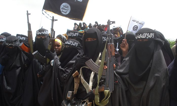 Somali women carry weapons during a demonstration organized by the Extremist group, Al-Shabaab, which is fighting the Somali government in Suqa Holaha neighborhood of Mogadishu on July 5, 2010. (ABDURASHID ABIKAR/AFP/File Photo via Getty Images)
