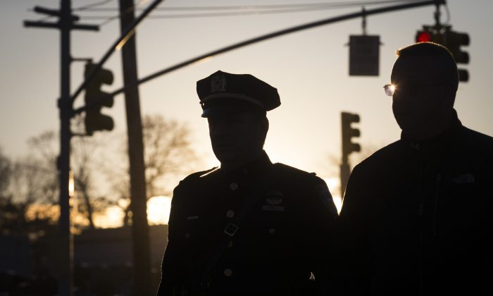 Police officers arrive at the funeral of New York City police officer Rafael Ramos in the Glendale section of Queens, Saturday, Dec. 27, 2014, in New York. Ramos and his partner, officer Wenjian Liu, were killed Dec. 20 as they sat in their patrol car on a Brooklyn street. The shooter, Ismaaiyl Brinsley, later killed himself. (AP Photo/John Minchillo)