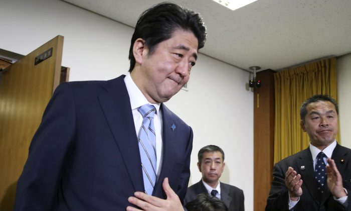 Japanese Prime Minister and leader of the ruling Liberal Democratic Party Shinzo Abe (L) arrives for a press conference at the party headquarters in Tokyo on Dec. 15, 2014. Japan's Cabinet on Saturday, Dec. 27, 2014, approved about 3.5 trillion yen ($29 billion) in fresh stimulus, including subsidies and job creation, to help pull the world's third-largest economy out of recession. (AP Photo/Koji Sasahara)