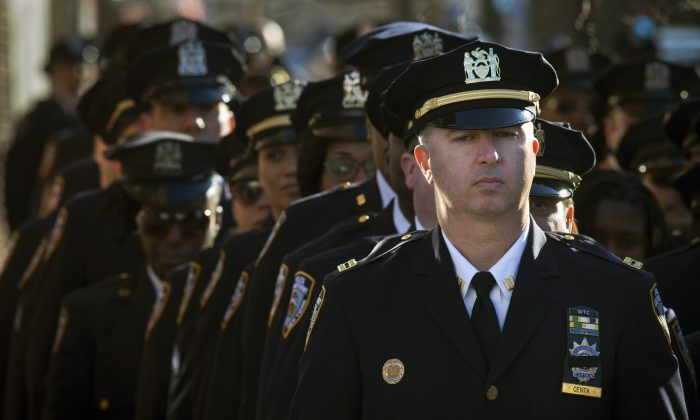 New York Police Department officers wait in line to enter the wake of officer Rafael Ramos at Christ Tabernacle Church, in the Glendale section of Queens, Friday, Dec. 26, 2014, in New York. Ramos was killed Dec. 20 along with his partner, Officer Wenjian Liu, as they sat in their patrol car on a Brooklyn street. The shooter, Ismaaiyl Brinsley, later killed himself. (AP Photo/John Minchillo)