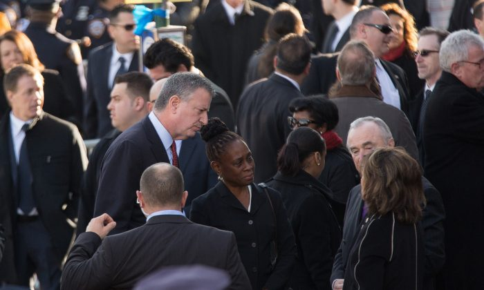 (L-R) New York Mayor Bill de Blasio, with his wife Chirlane McCray, greet Police Commissioner Bill Bratton and his wife Rikki Klieman outside the funeral of slain New York Police Department (NYPD) officer Rafael Ramos at the Christ Tabernacle Church in New York City on Dec. 27, 2014. (Kevin Hagen/Getty Images)