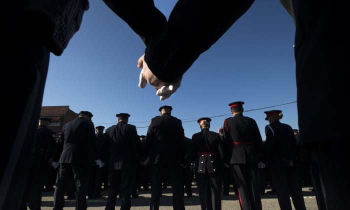 Police officers hold hands in prayer during the funeral service of New York City police officer Rafael Ramos in the Glendale section of Queens, Saturday, Dec. 27, 2014, in New York. Ramos and his partner, officer Wenjian Liu, were killed Dec. 20 as they sat in their patrol car on a Brooklyn street. The shooter, Ismaaiyl Brinsley, later killed himself. (AP Photo/John Minchillo)