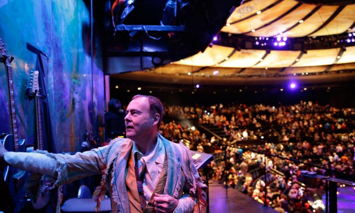 """Bruce Rickerd hangs up his guitar after a performance of the show """"Mystere"""" in Las Vegas on Dec. 17, 2014. On Saturday, Dec. 27, 2014, a Guinness Book of World Records judge is expected to say Rickerd has broken the record from most theatrical performances by a male musician. (AP Photo/John Locher)"""