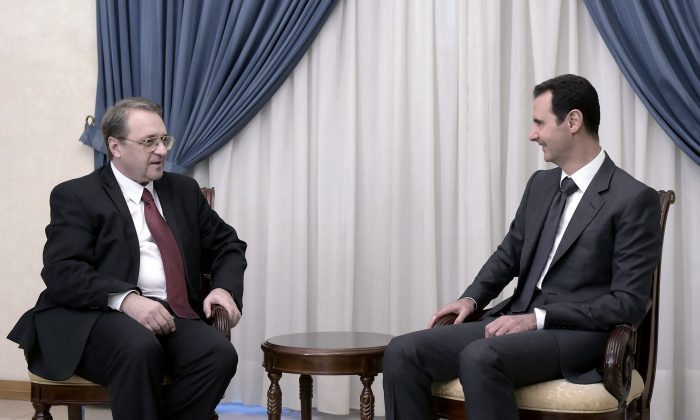 Syrian President Bashar Assad, right, meets with Russia's deputy Foreign Minister Mikhail Bogdanov in Damascus, Syria, Wednesday, Dec. 10, 2014. (AP Photo/SANA)