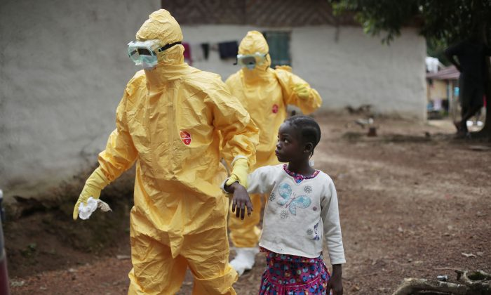 This Sept. 30, 2014 file photo shows Nowa Paye, 9, as she is taken to an ambulance after showing signs of Ebola infection in the village of Freeman Reserve, about 30 miles north of Monrovia, Liberia. (AP Photo/Jerome Delay)