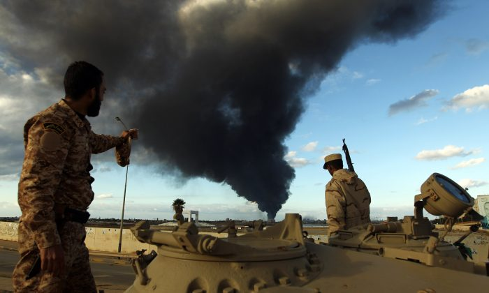 Members of the Libyan army stand on a tank as heavy black smoke rises from the city's port in the background after a fire broke out at a car tyre disposal plant during clashes against Islamist gunmen in the eastern Libyan city of Benghazi on Dec. 23, 2014. Forces loyal to former general Khalifa Haftar and to internationally recognised Prime Minister Abdullah al-Thani have been battling for weeks against Islamists who have taken control of much of Libya's second city, and the capital Tripoli. (Abdullah Doma/AFP/Getty Images)