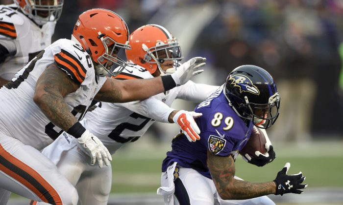 Baltimore Ravens wide receiver Steve Smith (89) tries to outrun Cleveland Browns defensive end Billy Winn, front left, and cornerback Joe Haden in the second half of an NFL football game in Baltimore on Dec. 28, 2014. (AP Photo/Nick Wass)