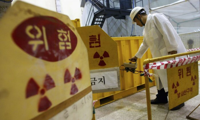A South Korean nuclear scientist tests a partly dismantled experimental reactor for radiation in part of at a Korea Atomic Energy Research Institute  in Seoul, South Korea, on Sept. 10, 2004. (Chung Sung-Jun/Getty Images)