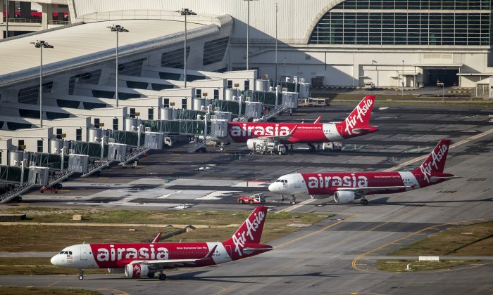 In this Nov 26, 2014 photo, AirAsia Airbus A320-200 passenger jets are parked on the tarmac at low cost terminal KLIA2 in Sepang, Malaysia. An AirAsia plane with 161 people on board lost contact with ground control on Sunday, Dec. 28, 2014, while flying over the Java Sea after taking off from a provincial city in Indonesia for Singapore, and search and rescue operations were underway. The planes in this photo are not the plane that went missing while flying from Indonesia to Singapore but one of the same models. (AP Photo/Vincent Thian)