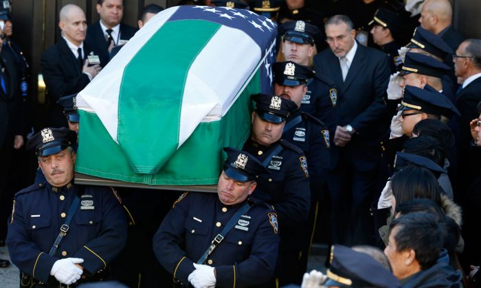Pallbearers carry the casket of New York City police officer Rafael Ramos outside Christ Tabernacle Church in Glendale, Queens, New York, after the funeral for slain officer Rafael Ramos was held on Dec. 27, 2014. (AP Photo/Julio Cortez)