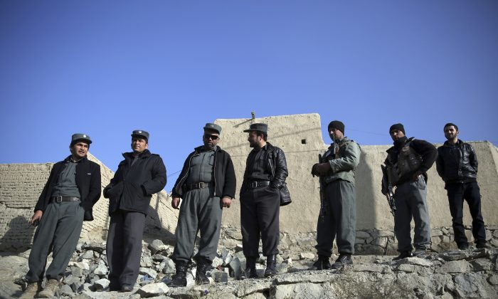 Afghanistan's police officers stand near the site of a suicide attack in Kabul, Afghanistan, on Dec. 11, 2014. (AP Photo/Massoud Hossaini)