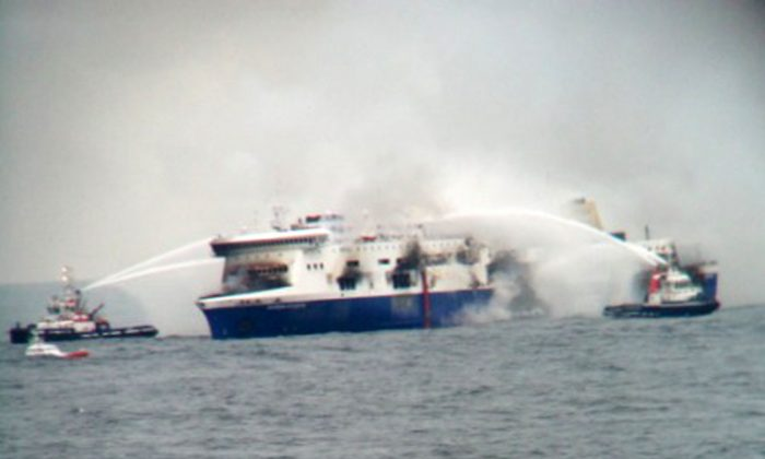 In this photo taken from a nearby ship, vessels try to extinguish the fire at the Italian-flagged Norman Atlantic after it caught fire in the Adriatic Sea, Sunday, Dec. 28, 2014. Italian and Greek military and coast guard rescue crews battled gale-force winds and massive waves Sunday as they struggled to rescue hundreds of people trapped on a burning ferry adrift between Italy and Albania. At least one person died and two were injured. The Italian Defense Ministry said 165 of the 478 people on the ferry had been evacuated by Sunday evening, more than 14 hours after the fire erupted. (AP Photo/SKAI TV Station)