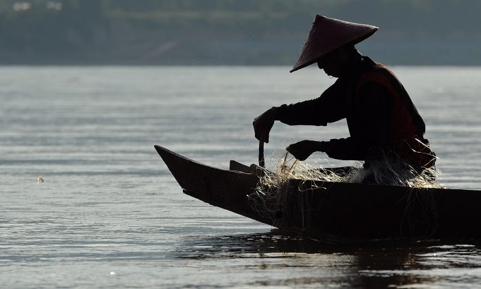 A fisherman pulls his net from the Mekong River in northern Thailand and bordering Laos on May 29, 2013. (Christophe Archambault/AFP/Getty Images)