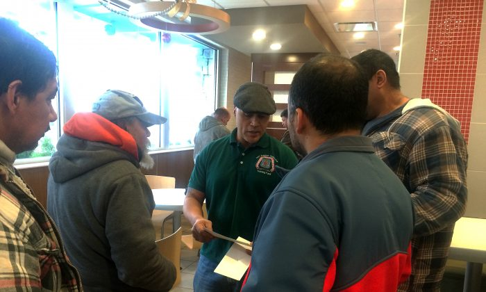 Manny Gines (2nd R), organizer for the New England Regional Council of Carpenters, speaks with three carpenters who recently received overdue wages after filing a complaint with the Attorney General's office, at a McDonald's in Boston, Mass., on Dec. 19, 2014. (Phoebe Ryles/Epoch Times)