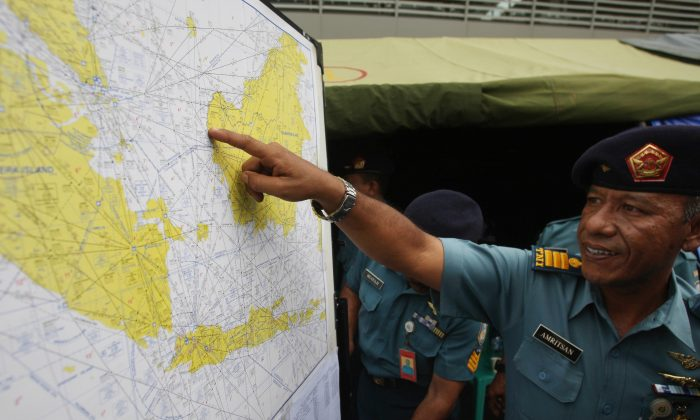 A military personnel points to a map of Indonesia at the crisis center set up by local authorities in search of the missing AirAsia flight QZ8501 at Juanda International Airport in Surabaya, East Java, Indonesia, Monday, Dec. 29, 2014. Search planes and ships from several countries on Monday were scouring Indonesian waters over which an AirAsia jet disappeared, more than a day into the region's latest aviation mystery. AirAsia Flight 8501 vanished Sunday in airspace thick with storm clouds on its way from Surabaya, Indonesia, to Singapore. (AP Photo/Trisnadi Marjan)
