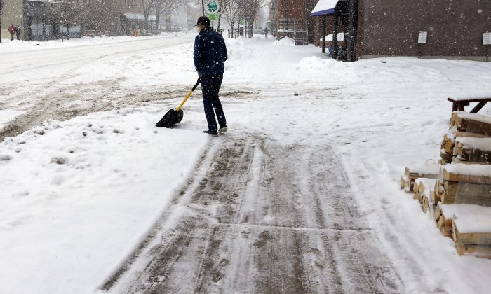 Scott Dygulski shovels snow in Boulder, Colo., Monday, Dec. 29, 2014. Colorado is getting hit by another wave of snow, this time with very cold weather in store. (AP Photo/Brennan Linsley)