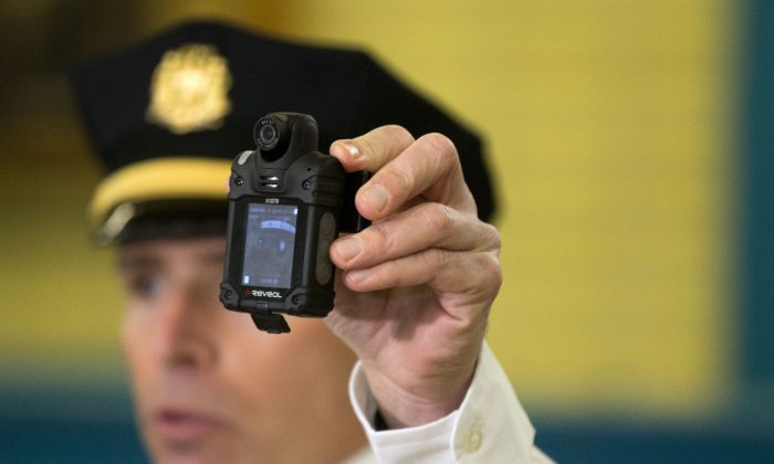 Philadelphia Police Lt. Thomas McLean demonstrates a body-worn camera being used as part of a pilot project in the department's 22nd District, Thursday, Dec. 11, 2014, in Philadelphia. (AP Photo/Matt Rourke)