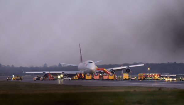 """Emergency services gather around a Virgin Atlantic Boeing passenger jet after it performed an emergency landing at Gatwick Airport following a landing gear fault, London, Monday, Dec. 29, 2014. The airline says the plane undertook """"a non-standard landing procedure"""" because of """"a technical issue with one of the landing gears."""" (AP Photo/PA, Gareth Fuller)"""