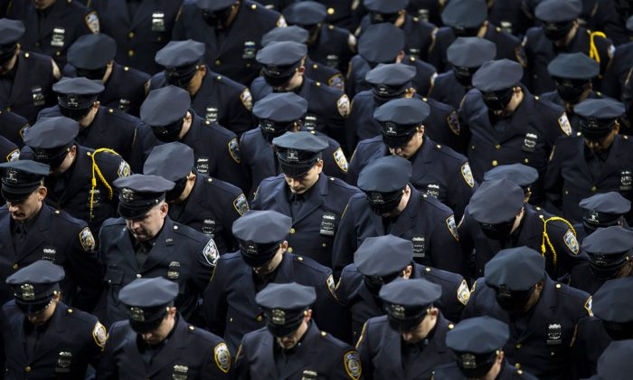 New recruits bow their heads in honor of deceased officers Rafael Ramos and Wenjian Liu during a New York Police Academy graduation ceremony, Monday, Dec. 29, 2014, at Madison Square Garden in New York. Nearly 1000 officers were sworn in as tensions between city hall and the NYPD continued following the Dec. 20 shooting deaths of officers Ramos and Liu. (AP Photo/John Minchillo)