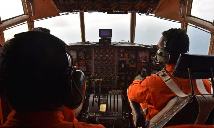 Indonesian air force personnel fly a C-130 Hercules aircraft over the Java Sea during search and rescue operations for missing AirAsia flight QZ8501 on Dec. 29, 2014. (Bay Ismoyo/AFP/Getty Images)