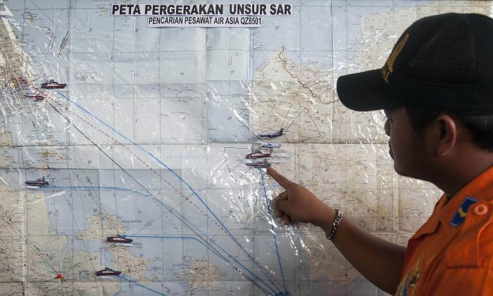 A search and rescue officer points to a co-ordination map of Indonesia at the crisis center set up by local authorities in search of the missing AirAsia flight QZ8501 at Juanda International Airport in Surabaya, East Java, Indonesia, Monday, Dec. 29, 2014. (AP Photo/Trisnadi Marjan)
