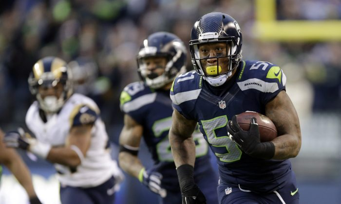 Seattle Seahawks linebacker Bruce Irvin, right, returns an interception for a touchdown against the St. Louis Rams in the second half of an NFL football game, Sunday, Dec. 28, 2014, in Seattle. (AP Photo/Scott Eklund)