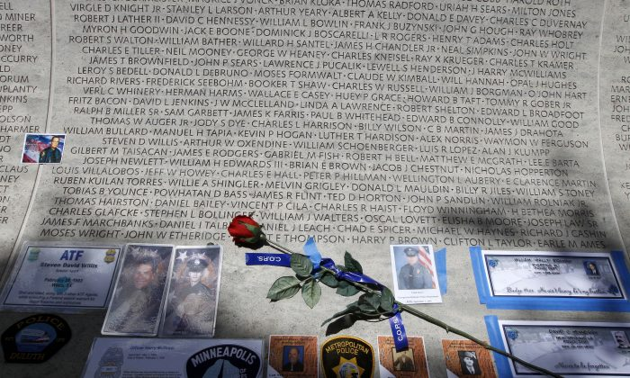 A rose is placed at the wall with the names of fallen police officers at the National Law Enforcement Officers Memorial in Washington during the National Police Week on May 13, 2013. The number of law enforcement officers killed by firearms in the US jumped by 56 percent this year and included 15 ambush assaults, according to a report released Tuesday. The annual report by the nonprofit National Law Enforcement Officers Memorial Fund found that 50 officers were killed by guns this year, compared to 32 in 2013. (AP Photo/Jose Luis Magana)
