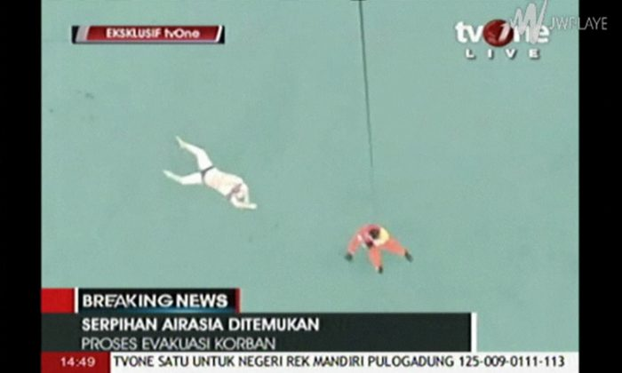 In this image taken from video released by TV One, a rescuer is lowered on rope from a hovering helicopter near a body in Java Sea waters, Indonesia Tuesday, Dec. 30, 2014.  Indonesian officials on Tuesday spotted six bodies from the AirAsia flight that disappeared two days earlier, and recovered three of them, in a painful end to the aviation mystery off the coast of Borneo island. (AP Photo/TV One via AP Video) TV OUT