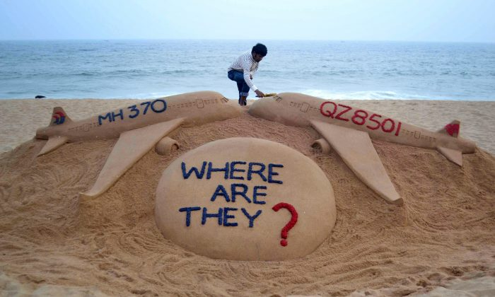 Indian sand artist Sudarsan Pattnaik gives the final touches to his sand sculpture portraying two missing aircraft, Air Asia QZ8501 and Malayasia Airlines MH370 on Golden Sea Beach at Puri, east of Bhubaneswar in a file photo. (STRDEL/AFP/Getty Images)