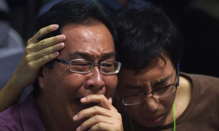 Family members of passengers onboard the missing Malaysian air carrier AirAsia flight QZ8501 react after watching news reports showing an unidentified body floating in the Java sea, inside the crisis-centre set up at Juanda International Airport in Surabaya on Dec. 30, 2014. (Manan Vatsyayana/AFP/Getty Images)