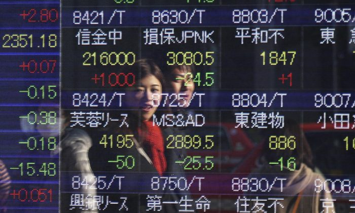 People are reflected on the electronic board of a securities firm in Tokyo, Tuesday, Dec. 30, 2014.  Asian stocks were mostly lower Tuesday as concern about Greek politics and the shaky Russian ruble dented confidence in the global economy.(AP Photo/Koji Sasahara)