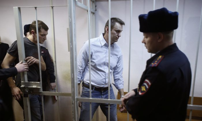 Russian opposition activist and anti-corruption crusader Alexei Navalny, 38, second right, and his brother Oleg Navalny, left, enter into the cage at a court in Moscow, Russia, Tuesday, Dec. 30, 2014. Alexei Navalny, the anti-corruption campaigner who is a leading foe of Russian President Vladimir Putin, has been found guilty of fraud and given a suspended sentence of three and a half years. (AP Photo/Pavel Golovkin)