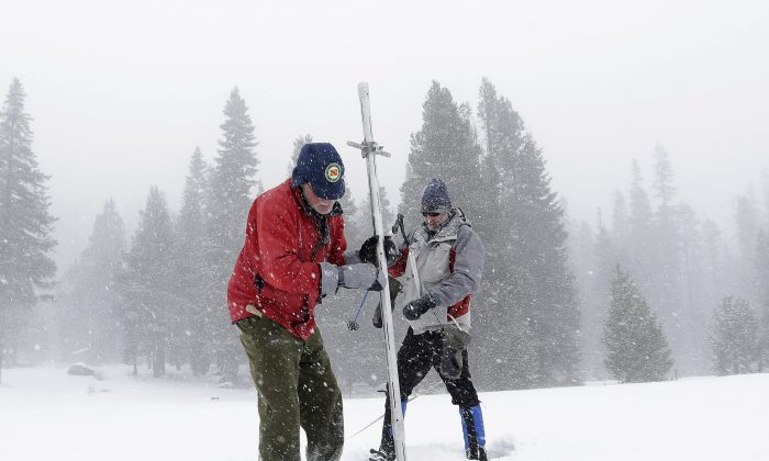 Frank Gehrke (L), chief of California Cooperative Snow Surveys Program for the Department of Water Resources, pulls the snow depth survey pole from the snow pack as he conducts the first snow survey of the season at Echo Summit, Calif., Tuesday, Dec. 30, 2014. The survey showed the snow pack to to be 21.3 inches deep with a water content of 4.8 inches, which is 33 percent of normal for this site at this time of year. At right is Dave Schmalenberger, of the Eat Bay Municipal Utility District, who accompanied Gehrke on the survey. (AP Photo/Rich Pedroncelli)