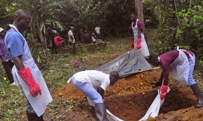 Ebola health care workers bury the body of a person suspected of dying of Ebola virus on the outskirts of Monrovia, Liberia, on Nov. 8, 2014. Ebola has killed more than 2,000 people in Sierra Leone and unsafe burials may be responsible for up to 70 percent of new infections, say experts. Officials are resorting to increasingly desperate measures to clamp down on traditional burials in Sierra Leone, where Ebola is now spreading fastest. The head of the Ebola response has even threatened to jail people who prepare the corpses of their loved ones. (AP Photo/Abbas Dulleh)