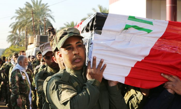 Mourners carry the coffin of retired Brig. Gen. Abbas Hassan Jabr, a senior member of the Badr Brigades, a Shiite militia, who was killed during a battle against the Islamic State extremist group, during his funeral in Baghdad Iraq, Thursday, Dec. 30, 2014. (AP Photo/Hadi Mizban)