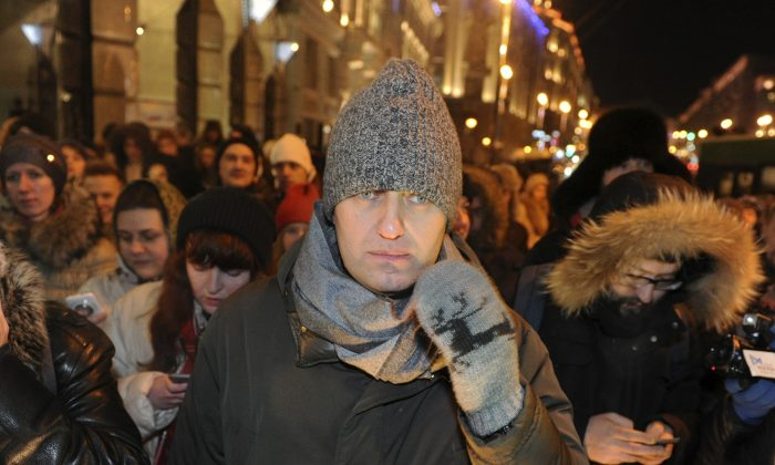 Russian opposition activist and anti-corruption crusader Alexei Navalny (C), 38, walks to attend a rally in Manezhnaya Square in Moscow, Russia, Tuesday, Dec. 30, 2014. The unsanctioned protest came hours after Alexei Navalny was found guilty of fraud and given a suspended sentence, while his brother was sent to prison. (AP Photo/Anton Belitski)