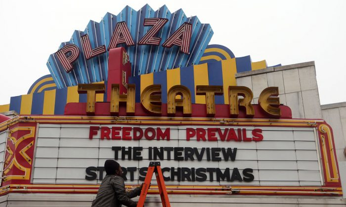 "Brandon Delaney, general manager of the Plaza Theatre, in Atlanta, Ga., finishes hanging the marquis on Dec. 23 to announce that the theater will be showing ""The Interview."" The film's video-on-demand debut coincided with its theatrical release, a first for a major studio picture. (AP Photo/Atlanta Journal-Constitution, Ben Gray)"