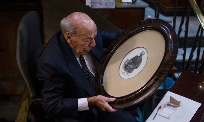 "Angel Garcia, 89, looks at a picture of former King of Spain, Alfonso XIII with his autograph, as he collects belongings during the shutdown of his store called ""Hernando"" after 57 years running in Madrid, Spain, on Dec. 29, 2014. About 200,000 mostly family-owned stores, bars and restaurants are affected by the law change that allows their landlords to raise rents to whatever they want. An estimated 55,000 businesses are expected to close down over the coming weeks and months, wiping out around 120,000 jobs in a country which already has a 24 percent unemployment rate, labor groups say. Supporters of the current lease holders say Spain will lose part of its cultural identity as international chain franchises take over the spaces. (AP Photo/Andres Kudacki)"