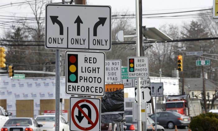 Traffic passes a red-light photo enforcement sign below a red-light camera in Lawrence Township, N.J., on Dec. 16, 2014. New Jersey legislators recently discontinued the state's red-light camera pilot program after five years. (AP Photo/Mel Evans)
