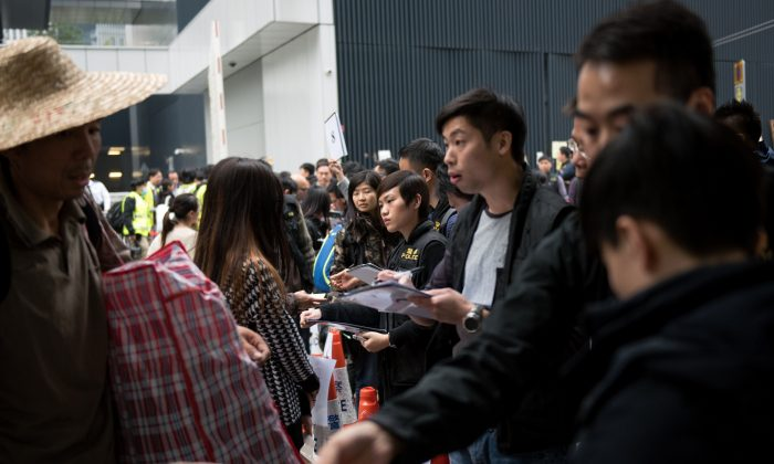 Hong Kong police (R) register people's identity cards as they are forced to leave what had been the main pro-democracy protest camp next to the central government offices in Hong Kong on December 11, 2014. (Alex Ogle/AFP/Getty Images)