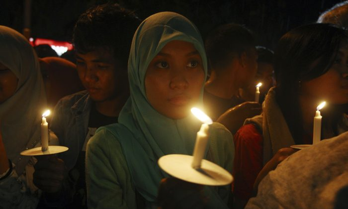 A flight attendant who was on AirAsia Flight QZ-8501, which crashed on Sunday morning, was the first to be buried. Hayati Lutfiah Hamid, who was identified via fingerprints and other means, was laid to rest on Thursday, according to local reports. The funeral took place in Surabaya, located in east Java.   Indonesians hold candles to pray for the victims of AirAsia Flight 8501 in Surabaya, Indonesia, Wednesday, Dec. 31, 2014. Bad weather hindered efforts to recover victims of the jetliner on Wednesday, and sent wreckage drifting far from the crash site, as grieving relatives prayed for strength to endure their losses. (AP Photo/Firdia Lisnawati)