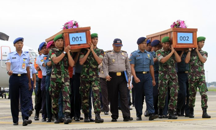 "Search and rescuers looking missing AirAsia Flight QZ-8501 off the coast of Indonesia bodies have recovered 30 bodies. Indonesian soldiers carry the bodies of victims of AirAsia Flight 8501 upon arrival at  Indonesian Military Air Force airport in Surabaya, Indonesia, Wednesday, Dec. 31, 2014. Bad weather hindered efforts to recover victims of the jetliner Wednesday, and sent wreckage drifting far from the crash site, as grieving relatives ""surrounded in darkness"" gathered in an airport and prayed for the strength to move forward. (AP Photo/Firdia Lisnawati)"