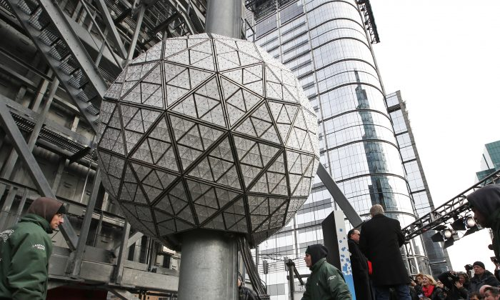 Workers prepare to test the Waterford crystal ball for the New Year's Eve celebration atop One Times Square in New York, Tuesday, Dec. 30, 2014. The ball, which is 12 feet in diameter and weighs 11,875 pounds, is decorated with 2,688 Waterford crystals and illuminated by 32,256 LED lights. (AP Photo/Kathy Willens)