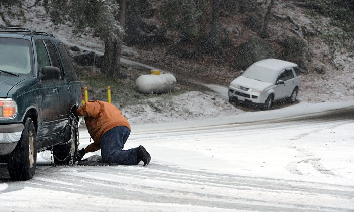 Jerry Walter, of Forest Falls, Calif., puts chains of his vehicle before heading to his home further up in the Southern California mountain community Tuesday Dec. 30, 2014. A very cold low-pressure system followed by an arctic airmass was dropping through the state, bringing the possibility of very low-elevation snow and blustery winds Tuesday night and early Wednesday and then a big chill through Thursday morning according to the National Weather Service. (AP Photo/The Sun, Rick Sforza)