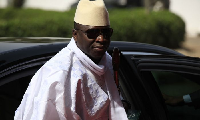 Gambia's President Yahya Jammeh arrives for a summit to address a seminar on security during an event marking the centenary of the unification of Nigeria's north and south in Abuja, Nigeria, on Feb. 27, 2014. Heavy gunfire is reported Tuesday Dec. 30, 2014, near the presidential palace in Gambia, according to local residents, raising the specter of a coup attempt while the longtime ruler is currently visiting France, state media reported. On Tuesday, soldiers linked to his presidential guard were believed to be involved in the fighting, according to witnesses who spoke on condition of anonymity for fear of reprisals. (AP Photo/Sunday Alamba)